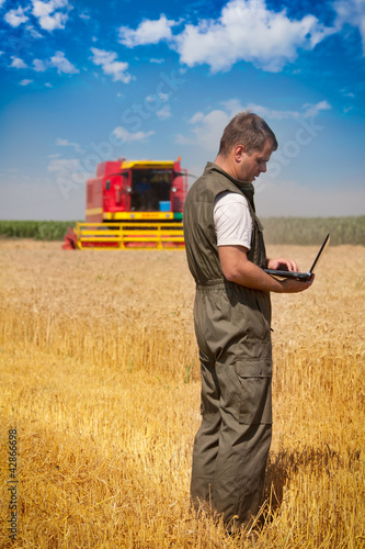 Farmer calculating earning in field