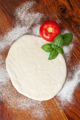Pizza dough with tomato and basil
