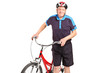 A senior bicyclist posing next to a bicycle