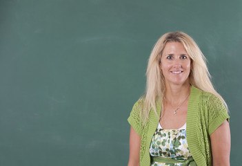 Teacher standing by chalkboard of classroom