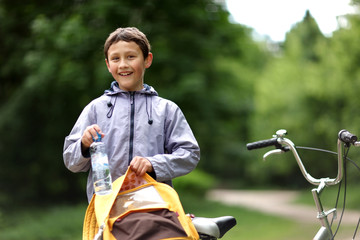 Young boy with bicycle with clear water relaxing outdoors