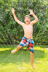 Endlich Sommer - Junge springt durch Wasserstrahl, Rasensprenger