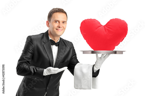 Butler holding a tray with a red heart shape object on it