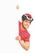 Portrait of a male bicyclist wearing helmet and posing behind a