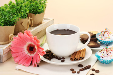 cup of coffee and gerbera  beans, cinnamon sticks