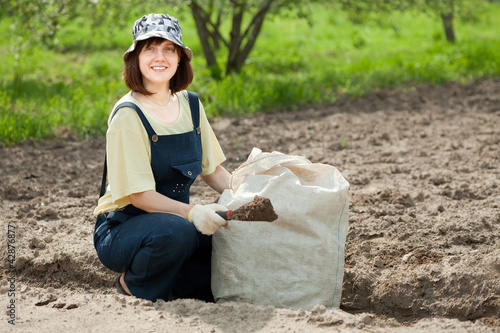 woman fertilizes  soil