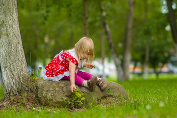 Adorable girl in beautiful dress sit on rock in park