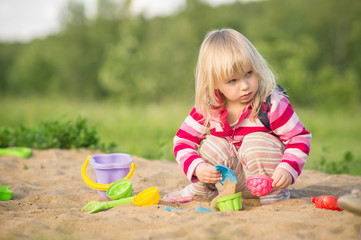 Adorable baby with bag play with toys on sandbox