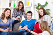 Group of teenagers sitting on sofa at home
