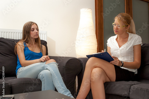 A sexy female psycotherapist treats a teenage female patien
