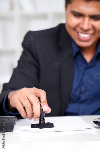 Businessman at his desk stamping
