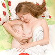 Mother is breast feeding baby in bed. Mother's love.
