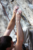 Closeup view of a rock climber's hands on a cliff