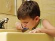 Niño cepillándose los dientes en un baño.lavando los dientes.