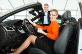 Young woman in seat of auto in car dealership