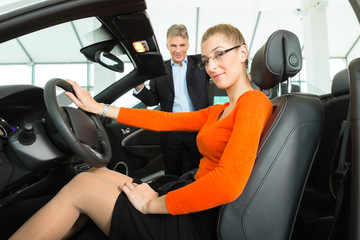 Junge Frau auf Fahrersitz eines Autos im Autohaus mit älterem Ma