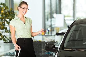 Junge Frau mit Autoschlüssel steht vor schwarzem Auto
