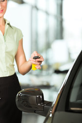 woman with car key opening new or rental auto