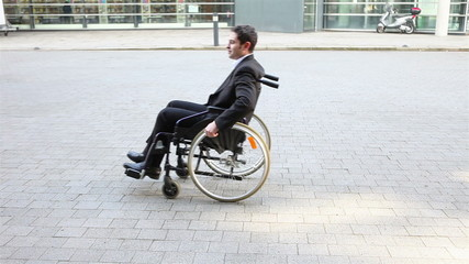 Business man rolling in wheelchair