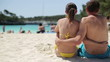 Couple sitting close together on the beach, tracking shot