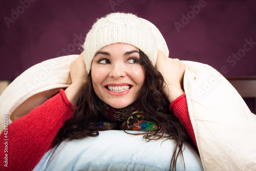 Happy woman peeking out from under blankets