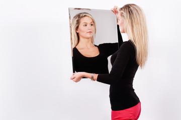 frau mädchen schaut in den spiegel zufrieden outfit