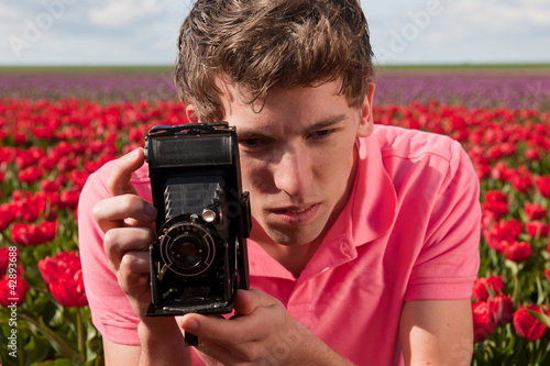 Young man with old photo camera in field with tulips