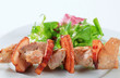 Pork skewer with salad greens