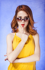 American redhead girl in sunglasses. Photo in 60s style.
