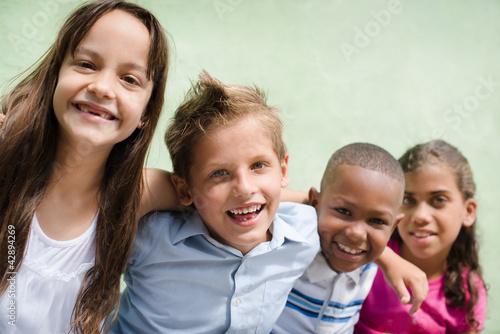 Leinwanddruck Bild happy children hugging, smiling and having fun