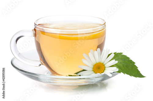Cup of tea with lemon slice, mint leaves and chamomile flower