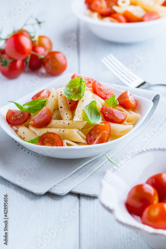 Pasta salad with fresh cherry tomatoes on kitchen table