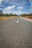 Woman is going through the road of outback, Australia
