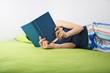 woman reading on green sheet
