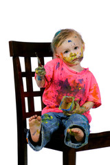 Toddler having fun sitting painting herself