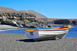 boat in a black sand beach in Ajuy, Fuerteventura, Spain