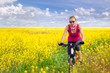 young woman cycling in canola field