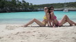 Two female friends sunbathing on the beach, tracking shot