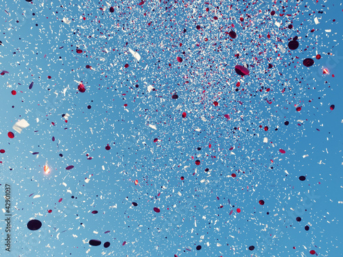 Red and White confetti against a blue sky