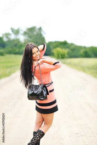Beautiful young girl with handbag posing near a copyspace