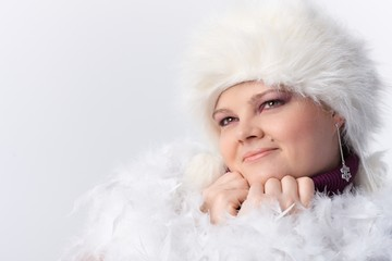 Plump woman among white feathers and fur