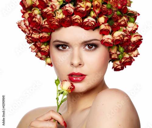 Portrait of young beautiful woman with roses in hair, on white b