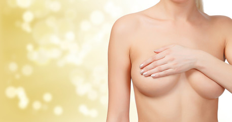Female controlling breast for cancer, gold blured background