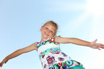 Bambina sorridente che gioca a volare