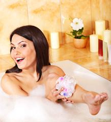 Woman relaxing in bubble bath .