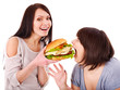 Women eating hamburger.