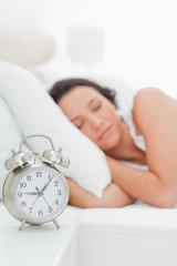 Close-up of a alarm clock with a woman sleeping