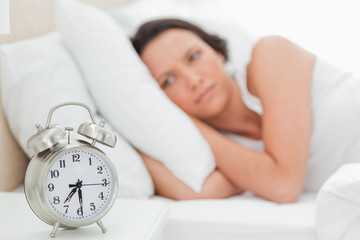 Alarm clock with a woman who just wakes up