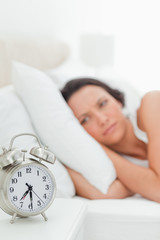 Close-up of an alarm clock with a woman who just wakes up
