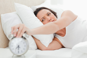 Woman turning off her alarm clock